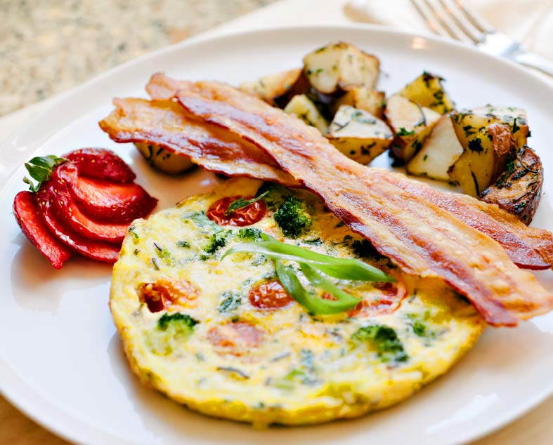 Amber House's farm fresh eggs in a summer frittata with bacon strips, roasted potatoes, and sliced strawberry