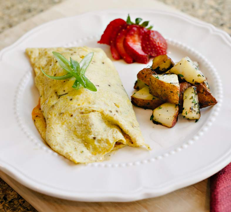 Omelets filled with sausage, vegetables, and cheese served with roasted potatoes and sliced strawberry